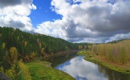 Fluss gegen Herbstwald mit den gelben und grünen Bäumen und heller bunter blauer Himmel mit Wolken stockfoto