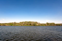 Fluss mit Bäumen auf einem Hintergrund des blauen Himmels Lizenzfreie Stockbilder