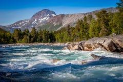 Fluss mit Bergen in der Rückseite Stockbilder