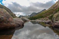 Fluss mit Berglandschaft auf Hintergrund Stockfotos
