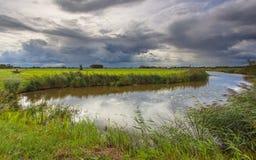 Fluss mit drastischen Wolken in Friesland, die Niederlande Lizenzfreies Stockbild