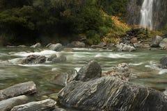 Fluss mit Felsen, milchigem Wasser und Wasserfall Stockbild