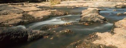Fluss mit Felsen und kleinen Wasserfällen Lizenzfreie Stockbilder