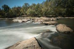 Fluss mit Felsen und kleinen Wasserfällen Stockbild