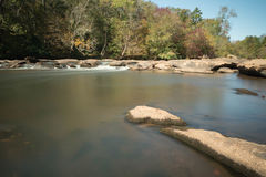 Fluss mit Felsen und kleinen Wasserfällen Lizenzfreie Stockfotos