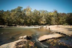 Fluss mit Felsen und kleinen Wasserfällen Stockfoto