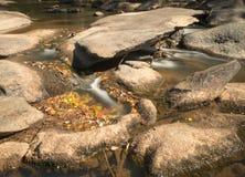 Fluss mit Felsen und kleinen Wasserfällen Stockbilder