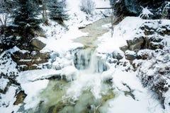 Fluss mit Wasserfall in den österreichischen Alpen am schneebedeckten Tag Stockfotografie