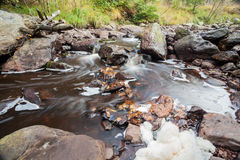 Fluss neben einem großen Flussstein Stockfotos