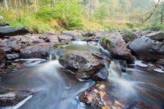 Fluss neben einem großen Flussstein Lizenzfreies Stockfoto