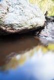 Fluss neben einem großen Flussstein Stockbild