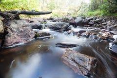 Fluss neben einem großen Flussstein Lizenzfreie Stockfotos