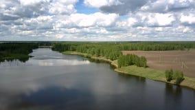 Fluss reflektiert Wolken nahe braunem Feld mit alten Stromleitungen stock video footage