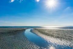 Fluss spaltete sich vom Ozean am sonnigen Tag des Strandes auf Stockbilder