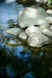 Fluss-Steine in einem Strom Stockbilder