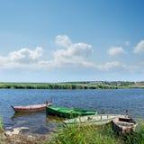 Fluss und alte Boote unter bewölktem Himmel Stockfoto