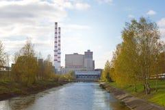 Fluss und ein Wasserkraftwerk Orangenblätter auf sogar grünem Gras Stockfoto