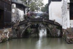 Fluss- und Steinbogenbrücke ist zwischen den Häusern Stockbild