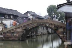 Fluss- und Steinbogenbrücke ist zwischen den houses〠 〠 Touristen im Regen Stockfotos
