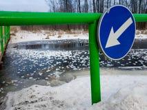 Fluss unter Brücke mit dünnem Eis und blauer Pfeil unterzeichnen Lizenzfreies Stockfoto