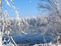 Fluss unter dem Eis und den Baumasten umfasst mit Reif Stockfotos