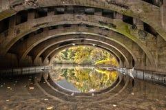 Fluss unter einer gewölbten Steinbrücke Stockfoto
