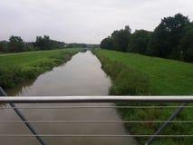 Fluss von einer Brücke im Regen mit grüner Natur in Deutschland Stockfotografie