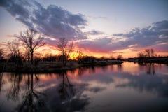 Fluss während des ruhig fließenden Sonnenuntergangs fließt den Frühlingswald im April durch Lizenzfreie Stockfotografie