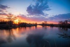 Fluss während des ruhig fließenden Sonnenuntergangs fließt den Frühlingswald im April durch Lizenzfreies Stockfoto