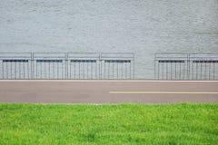 Fluss, Wiese, Straße und Baluster lizenzfreie stockfotografie