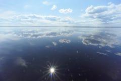 Flussansicht mit Wolken reflektierte sich in ihr, in der Sonne im Rahmen und in der Reflexion der Sonne, Volga, Russland Lizenzfreie Stockfotos