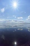 Flussansicht mit Wolken reflektierte sich in ihr, in der Sonne im Rahmen und in der Reflexion der Sonne, Volga, Russland Lizenzfreies Stockfoto