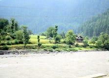 Flussbank mit kleinem Dorf und enorme wilde Berge auf der Rückseite Gebirgstal mit einem Fluss und einem Dorf lizenzfreie stockfotos