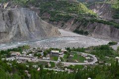 Flussbank mit kleinem Dorf und enorme wilde Berge auf der R?ckseite Gebirgstal mit einem Fluss und einem Dorf lizenzfreies stockfoto