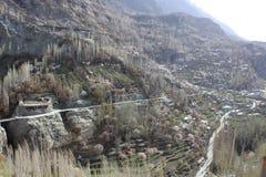 Flussbank mit kleinem Dorf und enorme wilde Berge auf der R?ckseite Gebirgstal mit einem Fluss und einem Dorf lizenzfreie stockfotografie