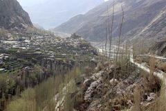 Flussbank mit kleinem Dorf und enorme wilde Berge auf der R?ckseite Gebirgstal mit einem Fluss und einem Dorf stockfotos