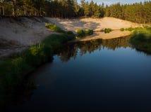 Flussbiegung im Wald auf dem Sonnenuntergang mit Reflexion Stockfotos