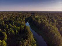 Flussbiegung im Wald auf dem Sonnenuntergang mit Reflexion Lizenzfreie Stockfotografie