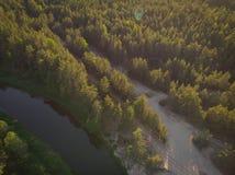 Flussbiegung im Wald auf dem Sonnenuntergang mit Reflexion Stockfotografie