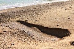Flussi di una molla dell'acqua dolce dalla spiaggia immagine stock