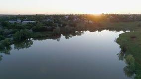 Flusslandschaft bei Sonnenuntergang, Brummenansicht zur Natur hinter Kleinstadt bei Sonnenuntergang stock video footage
