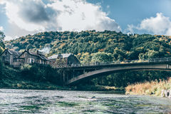 Flusslandschaft mit alter Brücke und Häusern Stockbilder