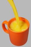Flusso arancione della spremuta e della tazza Immagini Stock
