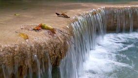 Flusso continuo dell'acqua della cascata tropicale e delle foglie variopinte Kanchanaburi, Tailandia archivi video
