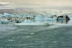 Flusso dal lago glacier di Jokulsarlon, Islanda Immagini Stock