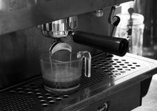 Flusso del caffè dalla macchina di caffè espresso Immagine Stock