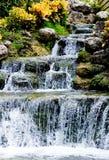 Flusso della cascata sopra le pietre e le piante crescenti fotografie stock libere da diritti