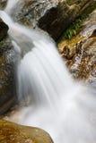 Flusso della montagna che funziona sopra le rocce Fotografie Stock