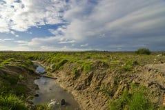 Flusso inquinante con il paesaggio ed i cieli blu Fotografie Stock Libere da Diritti
