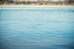 Flussoberfläche mit kleinen Kräuselungen im Vorfrühling Selektiver Fokus lizenzfreie stockbilder